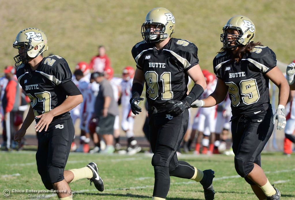 . Butte College\'s #27 Rigoberto Sanchez, #91 Mike Fratianni, and #99 Leopeni Siania (left to right) come off the field against City College of San Francisco in the second quarter of their football game at Butte\'s Cowan Stadium Saturday, November 16, 2013 in Butte Valley, Calif.  (Jason Halley/Chico Enterprise-Record)