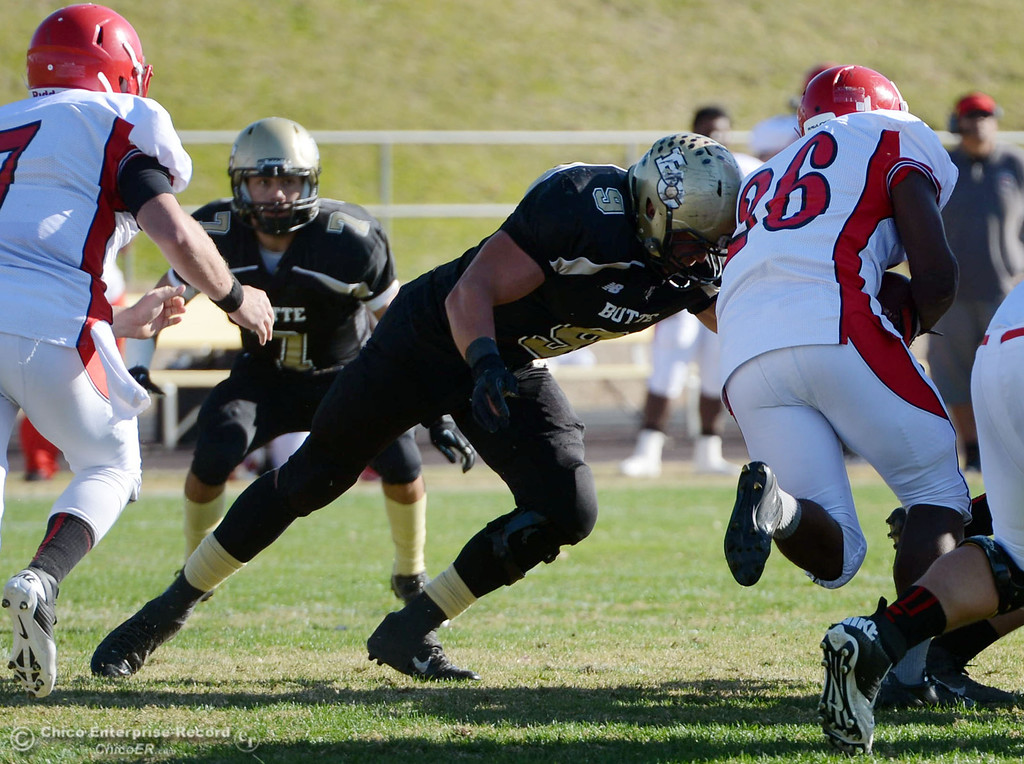 . Butte College\'s #9 Tyler Adair (left) tackles against City College of San Francisco\'s #26 Jahray Hayes (right) in the first quarter of their football game at Butte\'s Cowan Stadium Saturday, November 16, 2013 in Butte Valley, Calif.  (Jason Halley/Chico Enterprise-Record)