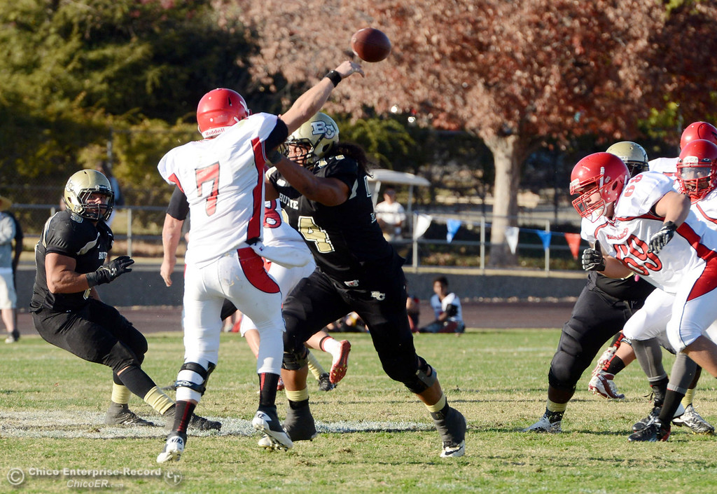 . Butte College\'s #74 Christopher Siliga (right) pressures against City College of San Francisco\'s #7 Turner Baty (left) in the third quarter of their football game at Butte\'s Cowan Stadium Saturday, November 16, 2013 in Butte Valley, Calif.  (Jason Halley/Chico Enterprise-Record)