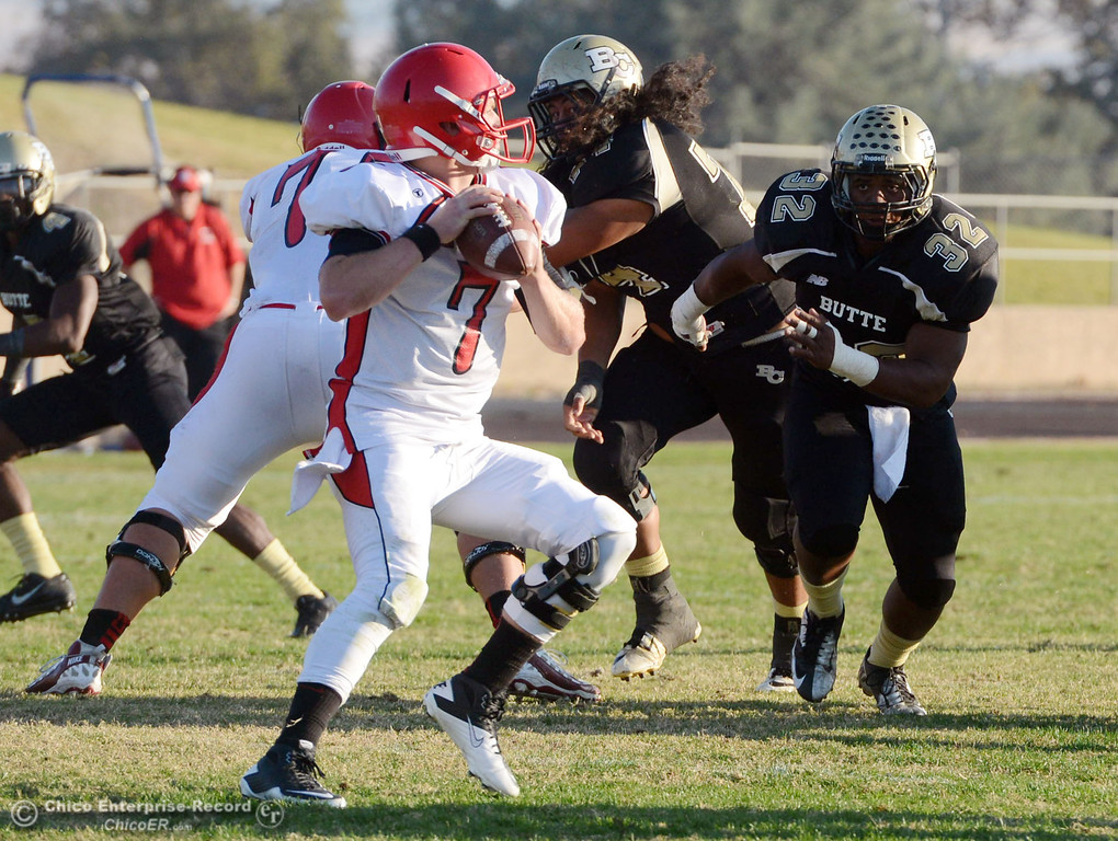 . Butte College\'s #32 Brian Anderson (right) puts pressure against City College of San Francisco\'s #7 Turner Baty (left) in the fourth quarter of their football game at Butte\'s Cowan Stadium Saturday, November 16, 2013 in Butte Valley, Calif.  (Jason Halley/Chico Enterprise-Record)
