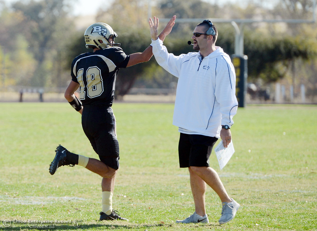 . Butte College\'s #18 Eric Ascensio (left) high fives coach Rob Snelling (right) against City College of San Francisco in the first quarter of their football game at Butte\'s Cowan Stadium Saturday, November 16, 2013 in Butte Valley, Calif.  (Jason Halley/Chico Enterprise-Record)