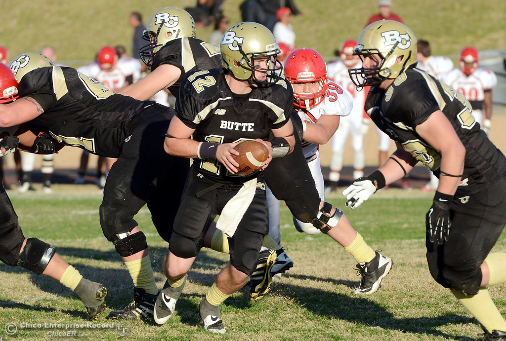 . Butte College\'s #12 Thomas Stuart (left) drops back for a handoff  against City College of San Francisco in the fourth quarter of their football game at Butte\'s Cowan Stadium Saturday, November 16, 2013 in Butte Valley, Calif.  (Jason Halley/Chico Enterprise-Record)