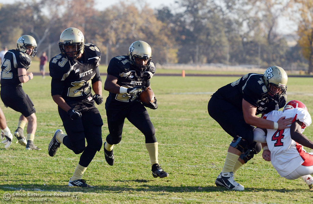 . Butte College\'s #23 Mykah Hester (left) leads ahead of #21 Marvel Harris (right) against City College of San Francisco in the fourth quarter of their football game at Butte\'s Cowan Stadium Saturday, November 16, 2013 in Butte Valley, Calif.  (Jason Halley/Chico Enterprise-Record)