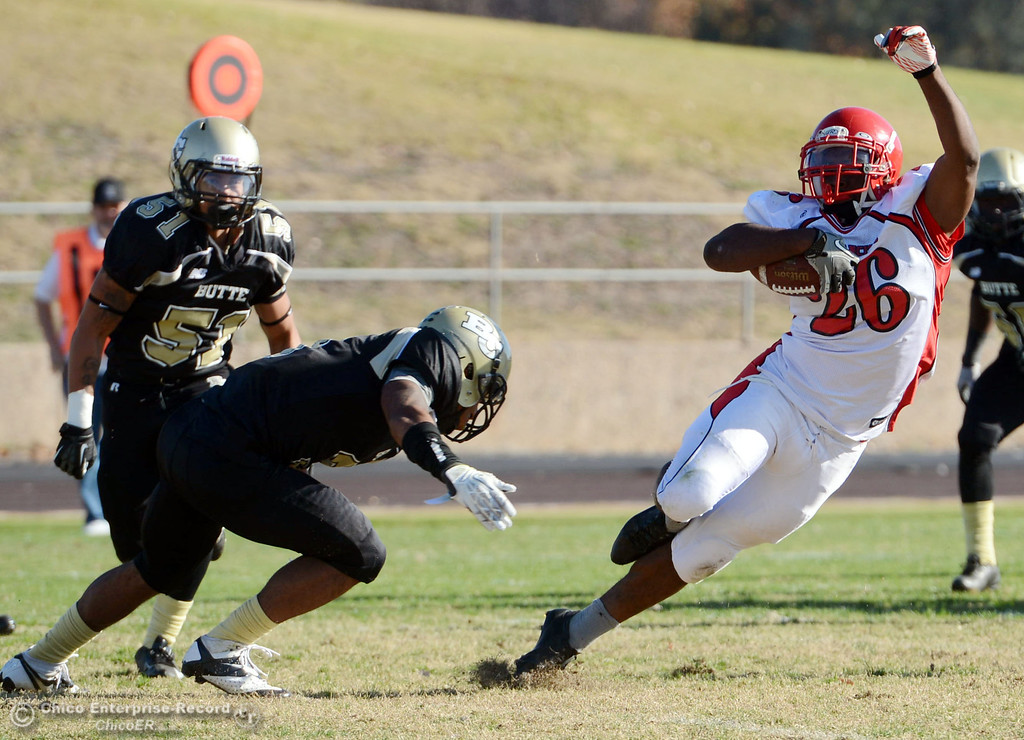 . Butte College\'s #3 London Muse (left) tackles against City College of San Francisco\'s #26 Jahray Hayes (right) in the second quarter of their football game at Butte\'s Cowan Stadium Saturday, November 16, 2013 in Butte Valley, Calif.  (Jason Halley/Chico Enterprise-Record)