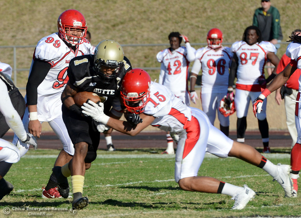 . Butte College\'s #1 Wes McCoy (left) is tackled against City College of San Francisco\'s #15 Shalom Luani (right) in the third quarter of their football game at Butte\'s Cowan Stadium Saturday, November 16, 2013 in Butte Valley, Calif.  (Jason Halley/Chico Enterprise-Record)