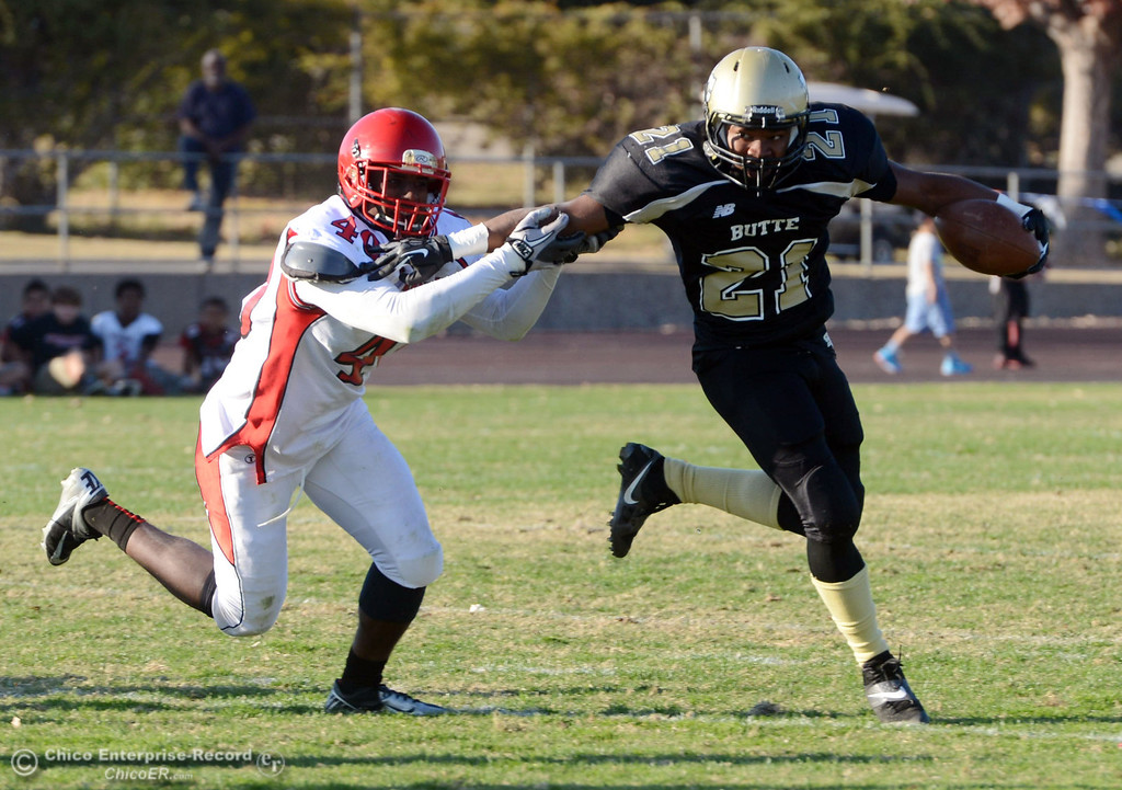 . Butte College\'s #21 Marvel Harris (right) rushes against City College of San Francisco\'s #40 Brendan Royal (left) in the third quarter of their football game at Butte\'s Cowan Stadium Saturday, November 16, 2013 in Butte Valley, Calif.  (Jason Halley/Chico Enterprise-Record)