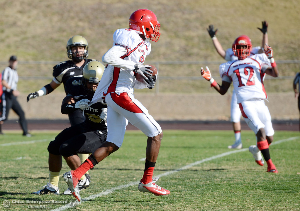 . City College of San Francisco\'s #8 Xavier Amey (right) scores a touchdown against Butte College\'s #3 London Muse (left) in the first quarter of their football game at Butte\'s Cowan Stadium Saturday, November 16, 2013 in Butte Valley, Calif.  (Jason Halley/Chico Enterprise-Record)