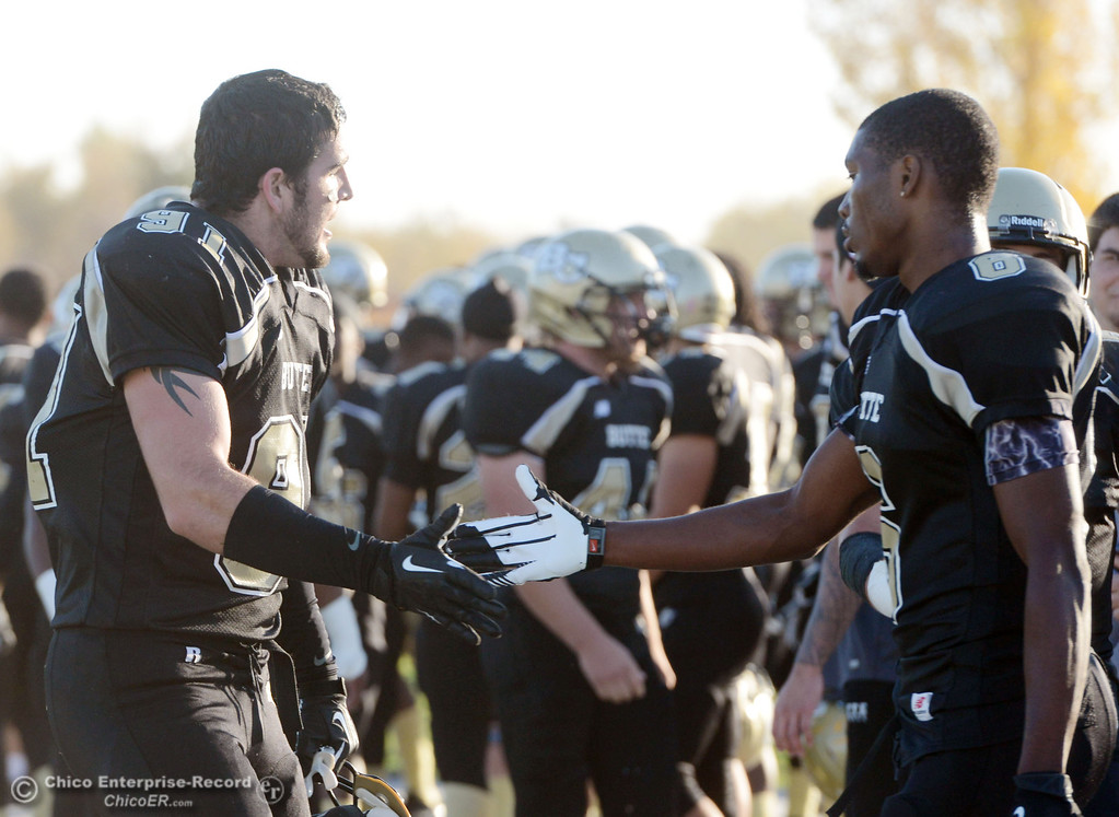 . Butte College\'s #91 Mike Fratianni (left) high fives #6 Denzel Conyers (right) against City College of San Francisco in the fourth quarter of their football game at Butte\'s Cowan Stadium Saturday, November 16, 2013 in Butte Valley, Calif.  (Jason Halley/Chico Enterprise-Record)