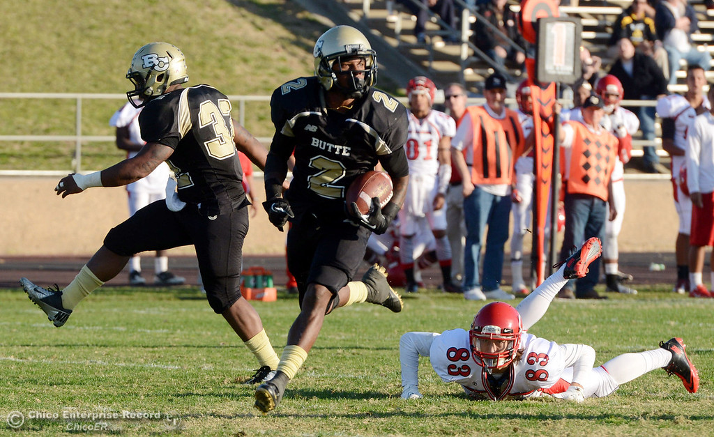 . Butte College\'s #2 Deonte Flemings (center) intercepts the ball to run for a touchdown against City College of San Francisco\'s #83 Dominic Gomes (right) in the fourth quarter of their football game at Butte\'s Cowan Stadium Saturday, November 16, 2013 in Butte Valley, Calif.  (Jason Halley/Chico Enterprise-Record)