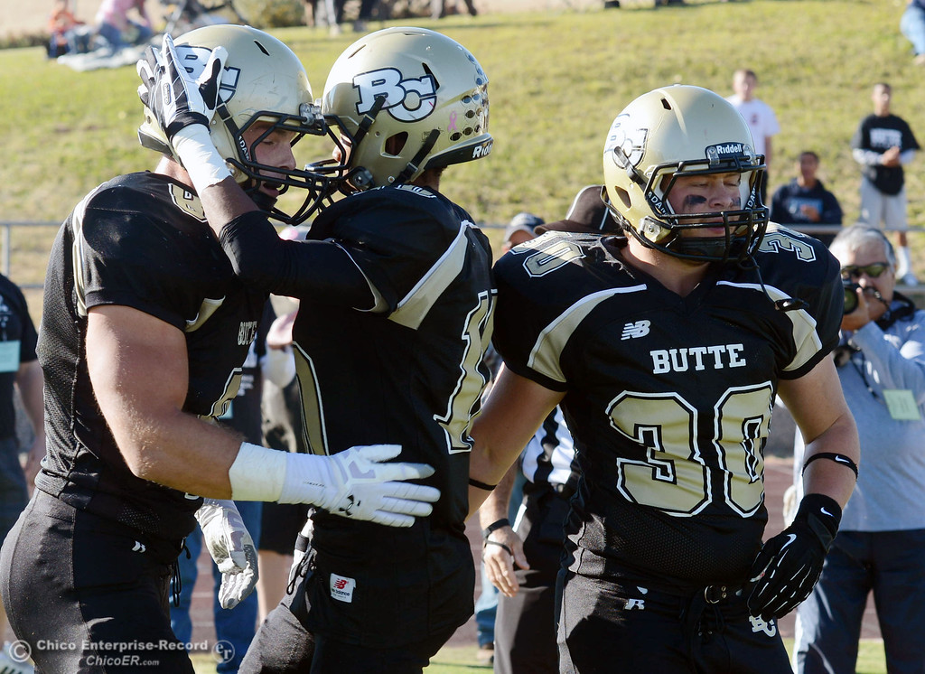 . Butte College\'s #8 Bo Brummel (left) is congratulated on scoring a touchdown by #10 CJ Grice and #30 Eric DeLucchi (right) against City College of San Francisco in the second quarter of their football game at Butte\'s Cowan Stadium Saturday, November 16, 2013 in Butte Valley, Calif.  (Jason Halley/Chico Enterprise-Record)
