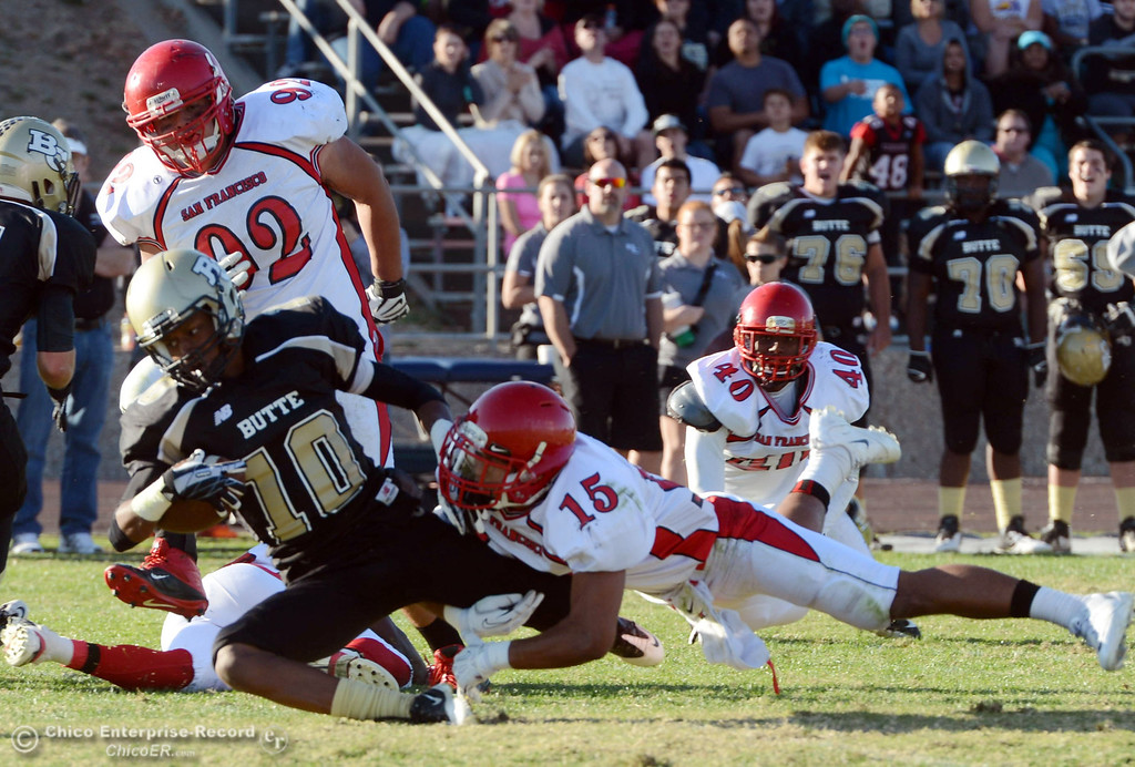 . Butte College\'s #10 CJ Grice (left) is tackled against City College of San Francisco\'s #15 Shalom Luani (right) in the third quarter of their football game at Butte\'s Cowan Stadium Saturday, November 16, 2013 in Butte Valley, Calif.  (Jason Halley/Chico Enterprise-Record)