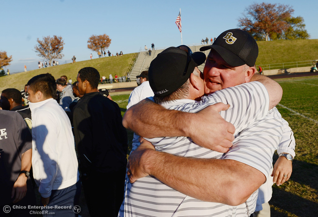 . Butte College coaches Willie Thomas and Thomas Flesher embrace to celebrate their win against City College of San Francisco at the end of their football game at Butte\'s Cowan Stadium Saturday, November 16, 2013 in Butte Valley, Calif.  (Jason Halley/Chico Enterprise-Record)