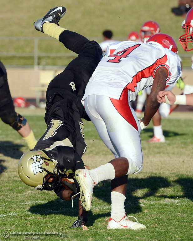 . Butte College\'s #14 Robert Frazier (left) is flipped over City College of San Francisco\'s #4 Maurice Cannon (right) in the fourth quarter of their football game at Butte\'s Cowan Stadium Saturday, November 16, 2013 in Butte Valley, Calif.  (Jason Halley/Chico Enterprise-Record)