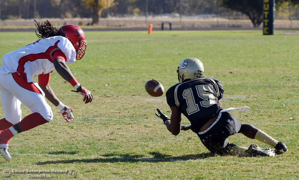 . Butte College\'s #15 Jalen Amis (right) catches against City College of San Francisco\'s #9 Uriah Harris (left) in the first quarter of their football game at Butte\'s Cowan Stadium Saturday, November 16, 2013 in Butte Valley, Calif.  (Jason Halley/Chico Enterprise-Record)