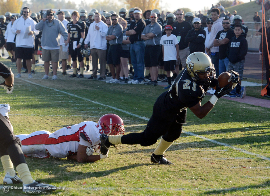 . Butte College\'s #21 Marvel Harris (right) leaps into the end zone to score against City College of San Francisco\'s #15 Shalom Luani (left) in the fourth quarter of their football game at Butte\'s Cowan Stadium Saturday, November 16, 2013 in Butte Valley, Calif.  (Jason Halley/Chico Enterprise-Record)