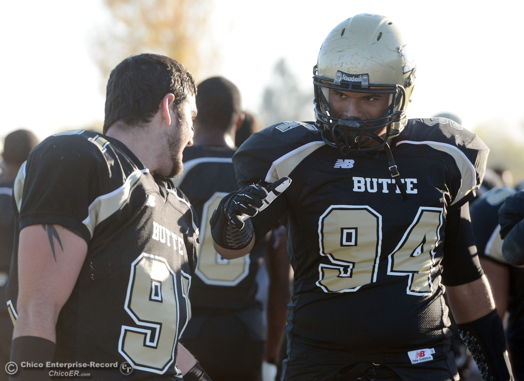 . Butte College\'s #91 Mike Fratianni (left) high fives #84 Shannon Dinsdale (right) against City College of San Francisco in the fourth quarter of their football game at Butte\'s Cowan Stadium Saturday, November 16, 2013 in Butte Valley, Calif.  (Jason Halley/Chico Enterprise-Record)