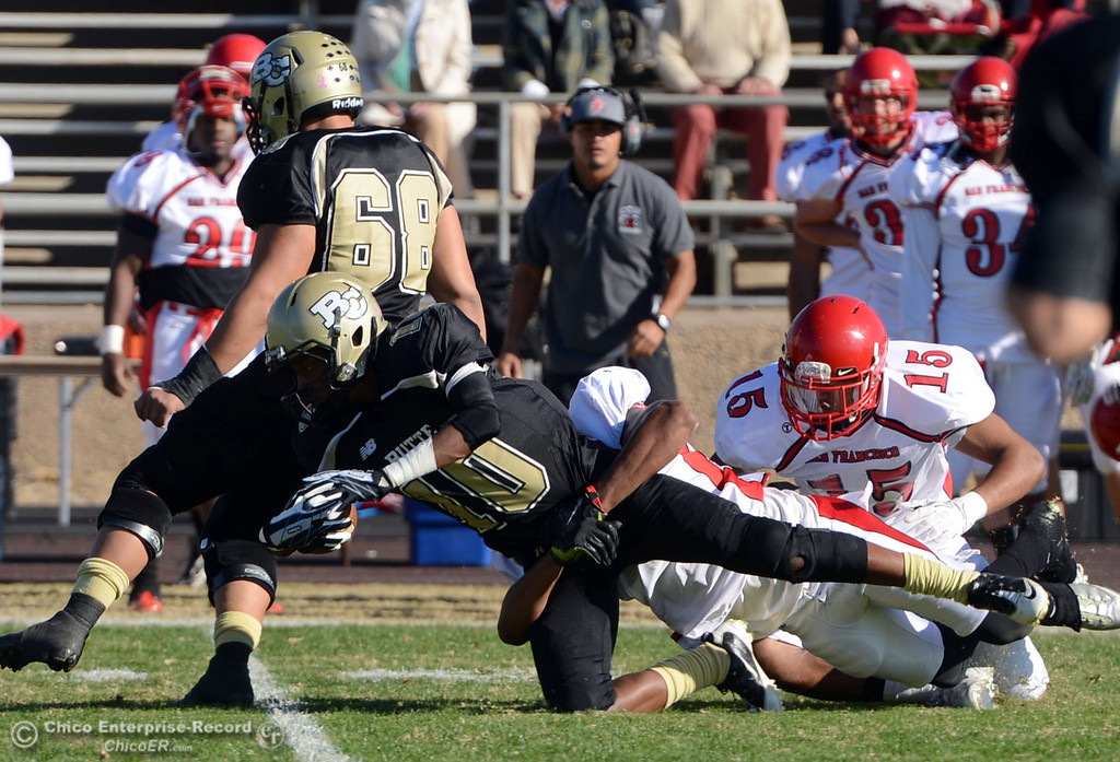 . Butte College\'s #10 CJ Grice is tackled by City College of San Francisco in the first quarter of their football game at Butte\'s Cowan Stadium Saturday, November 16, 2013 in Butte Valley, Calif.  (Jason Halley/Chico Enterprise-Record)