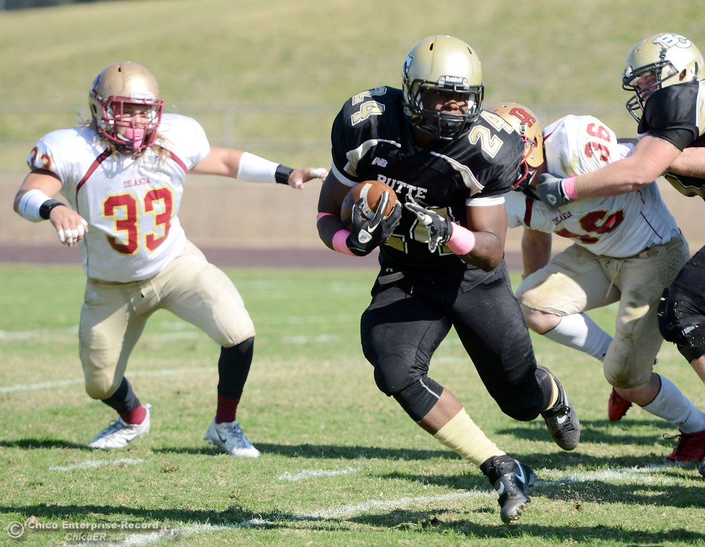 . Butte College\'s #24 Kendall Williams (right) rushes against De Anza College\'s #33 Chuck Sullivan (left) in the second quarter of their football game at Butte\'s Cowan Stadium Saturday, October 26, 2013 in Oroville, Calif.  (Jason Halley/Chico Enterprise-Record)