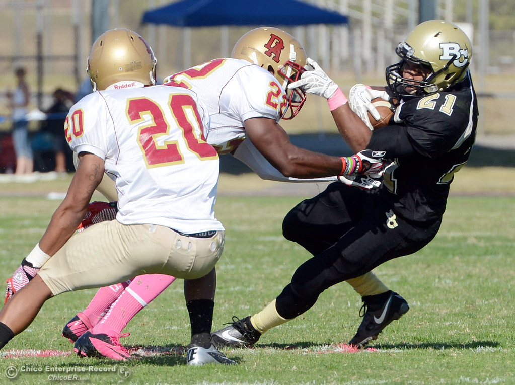 . Butte College\'s #21 Marvel Harris (right) is tackled against De Anza College\'s #22 Nathan Nelson (center) and #20 Kyree Rhodes (left) in the second quarter of their football game at Butte\'s Cowan Stadium Saturday, October 26, 2013 in Oroville, Calif.  (Jason Halley/Chico Enterprise-Record)