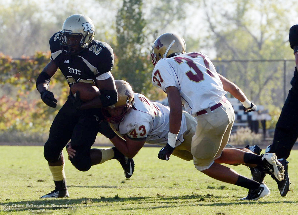 . Butte College\'s #22 Quinta Thomas (left) is tackled against De Anza College\'s #43 Mark Amann (center) and #37 Jeremy Imlach (right) in the fourth quarter of their football game at Butte\'s Cowan Stadium Saturday, October 26, 2013 in Oroville, Calif.  (Jason Halley/Chico Enterprise-Record)