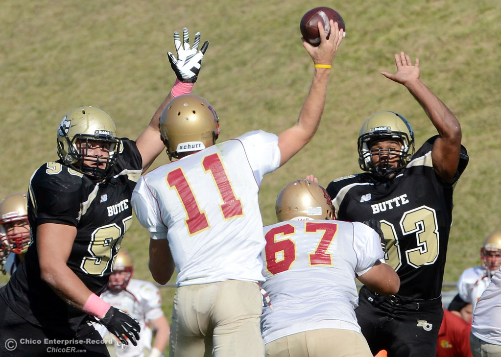 . Butte College\'s #95 MarkRosenquist (left) and #33 Jariah Booker (right) block a pass against De Anza College\'s #11 Jack Singler (center) in the second quarter of their football game at Butte\'s Cowan Stadium Saturday, October 26, 2013 in Oroville, Calif.  (Jason Halley/Chico Enterprise-Record)
