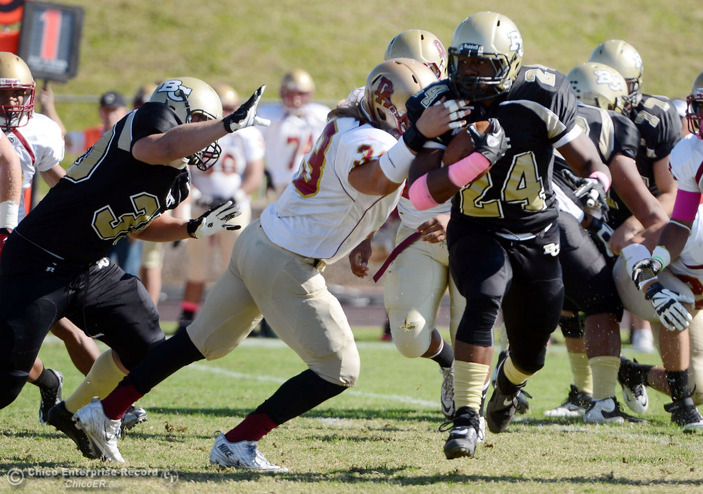 . Butte College\'s #24 Kendall Williams (right) rushes against De Anza College\'s #33 Chuck Sullivan (left) in the first quarter of their football game at Butte\'s Cowan Stadium Saturday, October 26, 2013 in Oroville, Calif.  (Jason Halley/Chico Enterprise-Record)