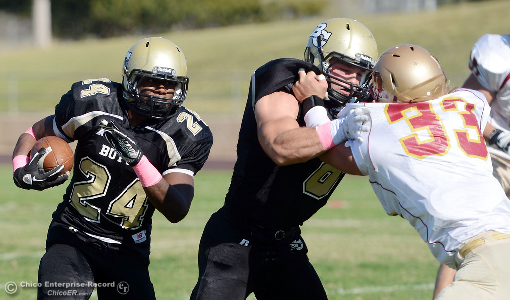. Butte College\'s #24 Kendall Williams (left) rushes on a block by #8 Bo Brummel (center) against De Anza College\'s #33 Chuck Sullivan (right) in the second quarter of their football game at Butte\'s Cowan Stadium Saturday, October 26, 2013 in Oroville, Calif.  (Jason Halley/Chico Enterprise-Record)
