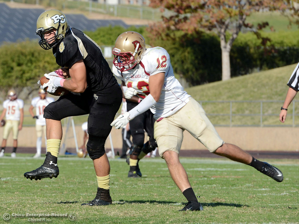 . Butte College\'s #8 Bo Brummel (left) breaks a tackle to score a touchdown against De Anza College\'s #12 Rodney McKenzie (right) in the third quarter of their football game at Butte\'s Cowan Stadium Saturday, October 26, 2013 in Oroville, Calif.  (Jason Halley/Chico Enterprise-Record)