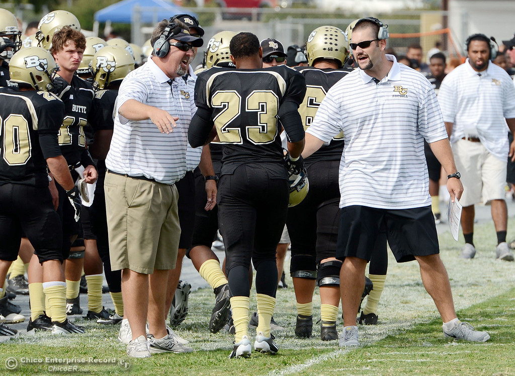 . Butte College\'s head coach Jeff Jordan (left) and Rob Snelling (right) congratulates #23 Mykah Hester and the team on a touchdown against Delta College in the third quarter of their football game at Butte\'s Cowan Stadium Saturday, September 28, 2013, in Oroville, Calif.  (Jason Halley/Chico Enterprise-Record)
