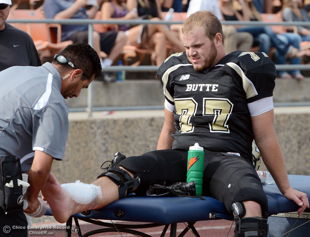 . Butte College\'s #77 Scott Batchelder is treated for an injury against Delta College in the third quarter of their football game at Butte\'s Cowan Stadium Saturday, September 28, 2013, in Oroville, Calif.  (Jason Halley/Chico Enterprise-Record)