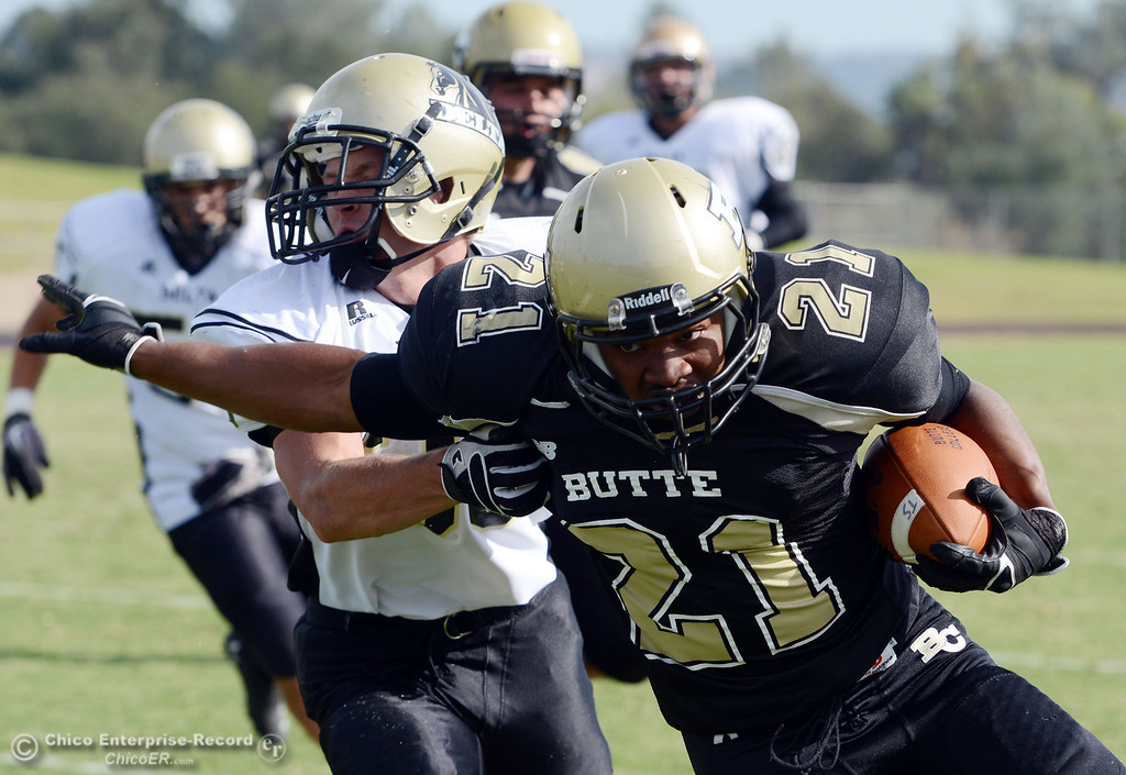 . Butte College\'s #21 Marvel Harris (right) is tackled against Delta College\'s #30 Andrew Truax (left) in the fourth quarter of their football game at Butte\'s Cowan Stadium Saturday, September 28, 2013, in Oroville, Calif.  (Jason Halley/Chico Enterprise-Record)