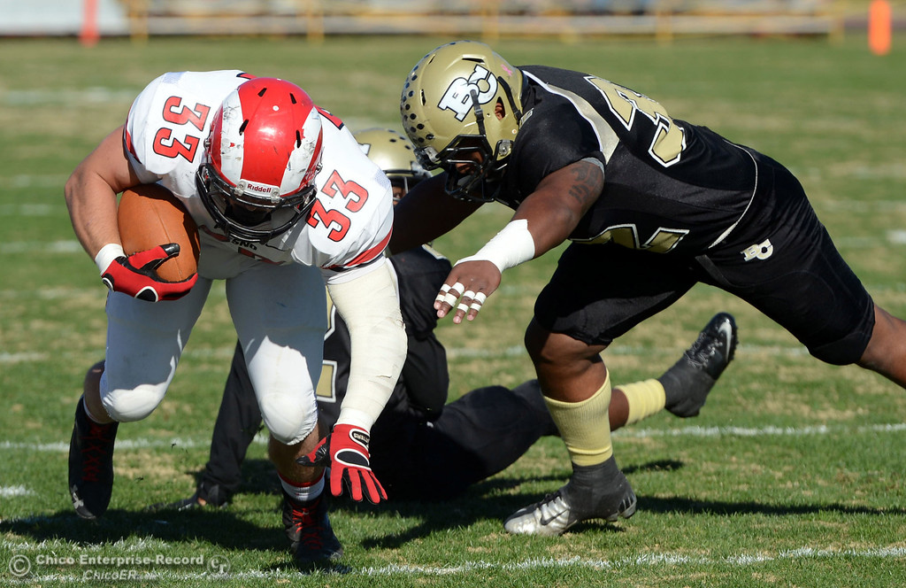 . Butte College\'s #32 Brian Anderson (right) tackles against Fresno City College\'s #33 Dakota Gordon (left) in the first quarter of their football game at Butte\'s Cowan Stadium Saturday, November 30, 2013 in Butte Valley, Calif.  (Jason Halley/Chico Enterprise-Record)