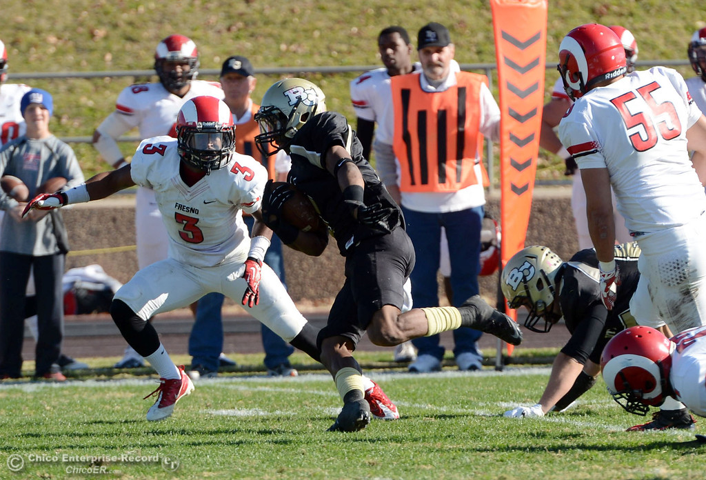 . Butte College\'s #1 Wes McCoy (center) runs for a touchdown against Fresno City College\'s #3 Marquise Cooper (left) in the first quarter of their football game at Butte\'s Cowan Stadium Saturday, November 30, 2013 in Butte Valley, Calif.  (Jason Halley/Chico Enterprise-Record)