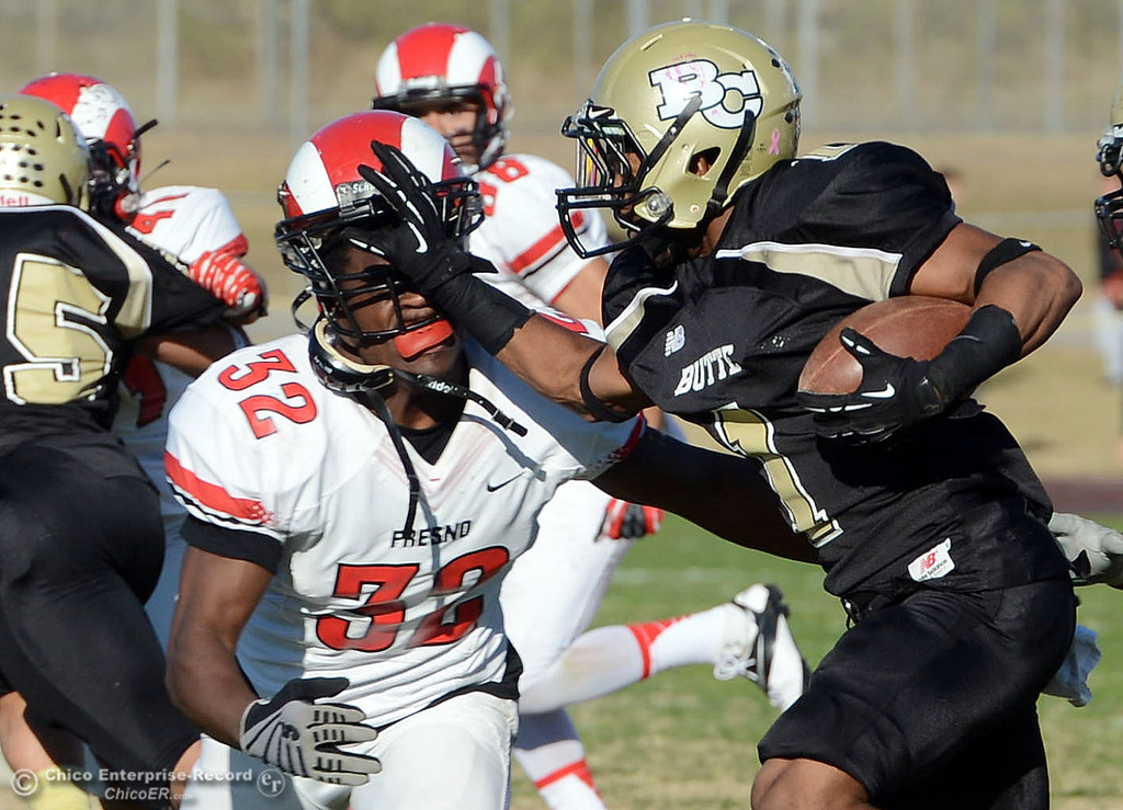 . Butte College\'s #1 Wes McCoy (right) puts up an arm against Fresno City College\'s #32 Eric Wingfield (left) in the third quarter of their football game at Butte\'s Cowan Stadium Saturday, November 30, 2013 in Butte Valley, Calif.  (Jason Halley/Chico Enterprise-Record)