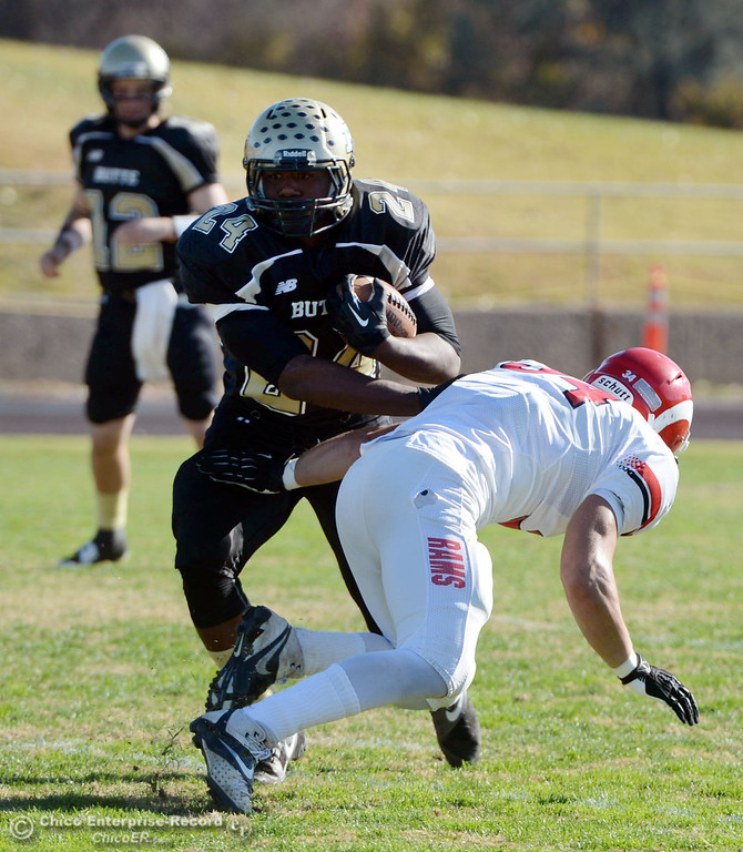 . Butte College\'s #24 Kendall Williams (left) breaks a tackle against Fresno City College\'s #34 Aaron Ley (right) in the first quarter of their football game at Butte\'s Cowan Stadium Saturday, November 30, 2013 in Butte Valley, Calif.  (Jason Halley/Chico Enterprise-Record)