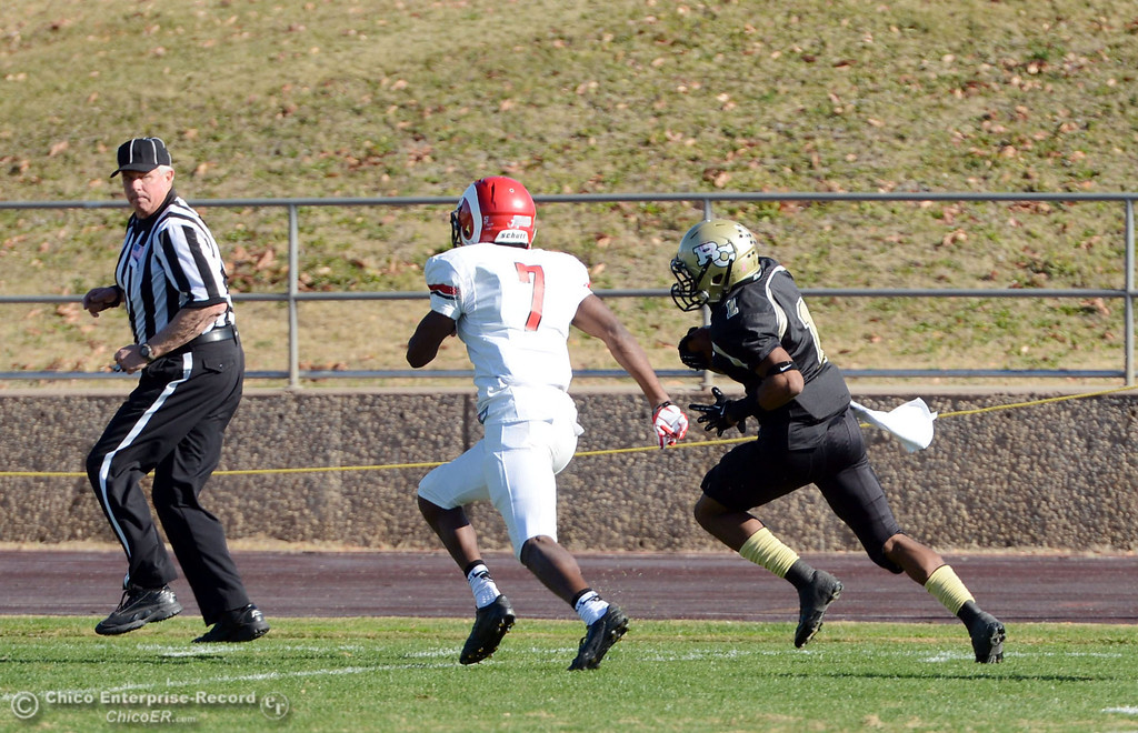 . Butte College\'s #1 Wes McCoy (right) runs for a touchdown against Fresno City College\'s #7 Vadal McDonald (left) in the first quarter of their football game at Butte\'s Cowan Stadium Saturday, November 30, 2013 in Butte Valley, Calif.  (Jason Halley/Chico Enterprise-Record)