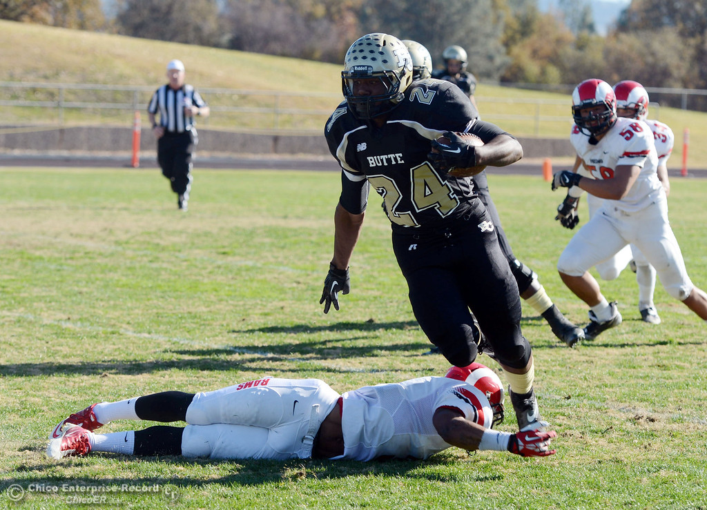 . Butte College\'s #24 Kendall Williams (right) is tackled against Fresno City College\'s #3 Marquise Cooper (left) in the first quarter of their football game at Butte\'s Cowan Stadium Saturday, November 30, 2013 in Butte Valley, Calif.  (Jason Halley/Chico Enterprise-Record)