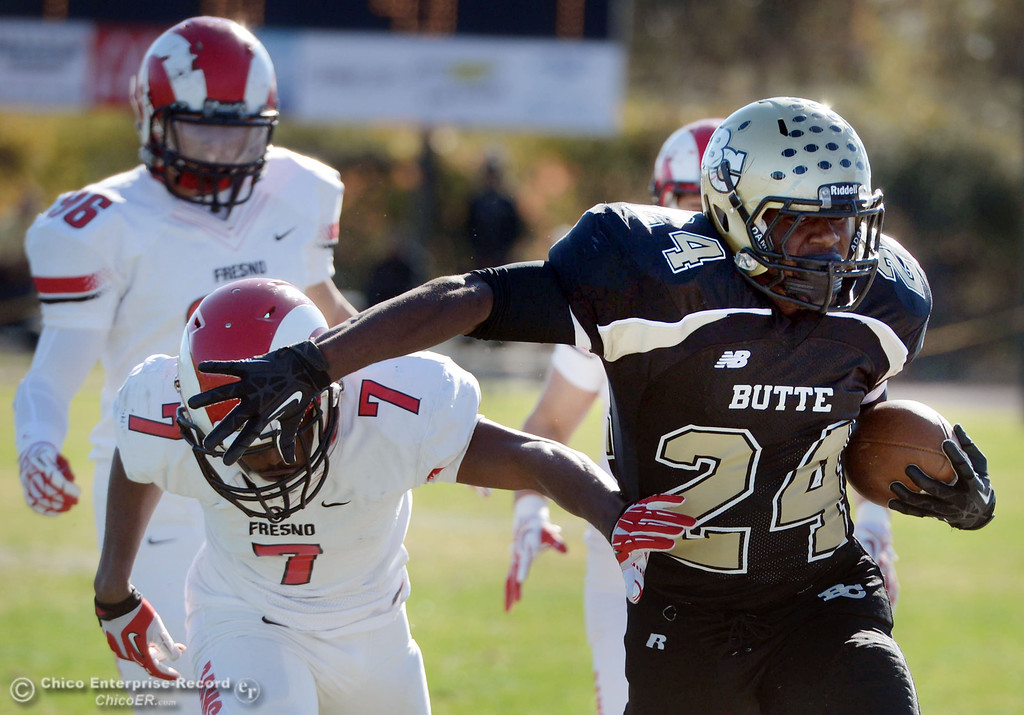 . Butte College\'s #24 Kendall Williams (right) is pushed out of bounds against Fresno City College\'s #7 Vadal McDonald (left) in the first quarter of their football game at Butte\'s Cowan Stadium Saturday, November 30, 2013 in Butte Valley, Calif.  (Jason Halley/Chico Enterprise-Record)
