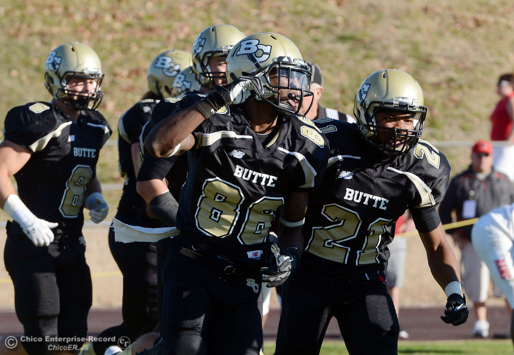 . Butte College\'s #86 Jon Parks (left) scored a touchdown as he comes off the field with #21 Marvel Harris (right) against Fresno City College in the third quarter of their football game at Butte\'s Cowan Stadium Saturday, November 30, 2013 in Butte Valley, Calif.  (Jason Halley/Chico Enterprise-Record)