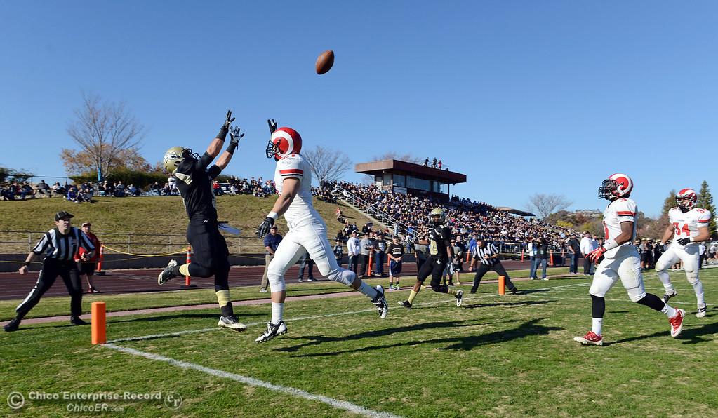 . Butte College\'s #5 David Brannon (left) attempts to make a catch against Fresno City College\'s #21 Garrett Steele (right), but catches out of bounds in the second quarter of their football game at Butte\'s Cowan Stadium Saturday, November 30, 2013 in Butte Valley, Calif.  (Jason Halley/Chico Enterprise-Record)