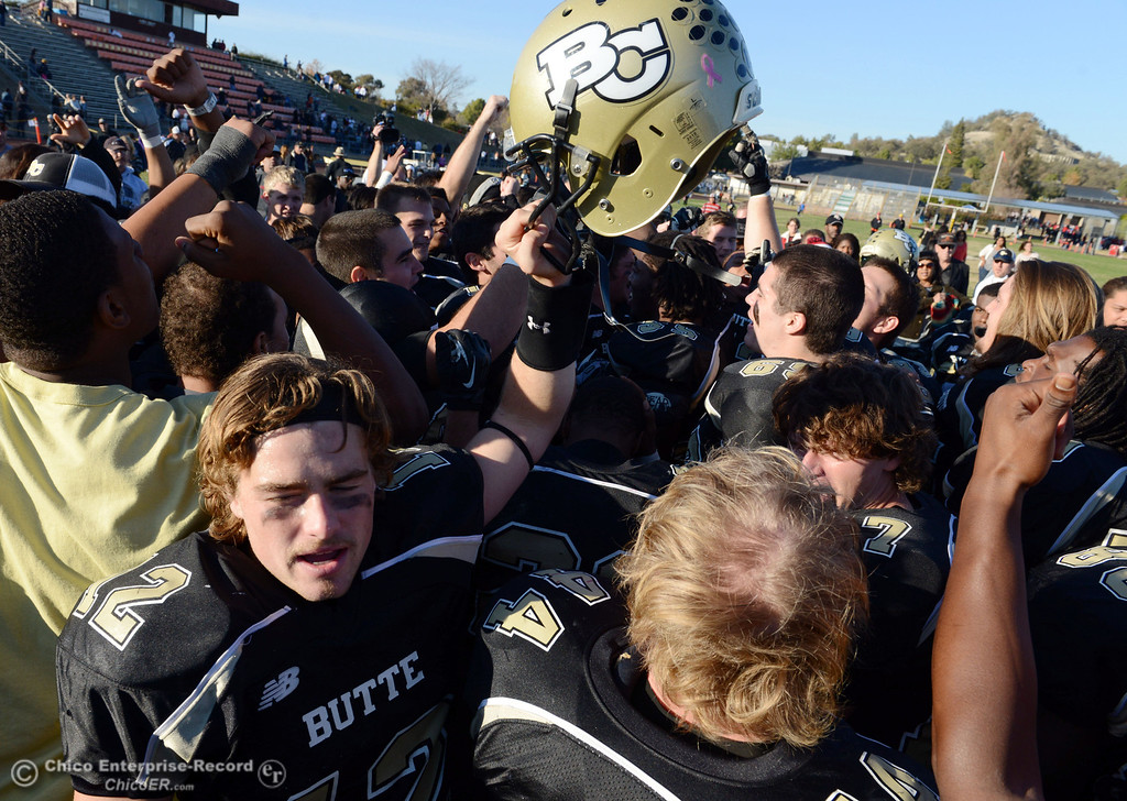 . Butte College\'s #12 Thomas Stuart (left) cheers with the team to celebrate their win against Fresno City College at the end of their football game at Butte\'s Cowan Stadium Saturday, November 30, 2013 in Butte Valley, Calif.  (Jason Halley/Chico Enterprise-Record)