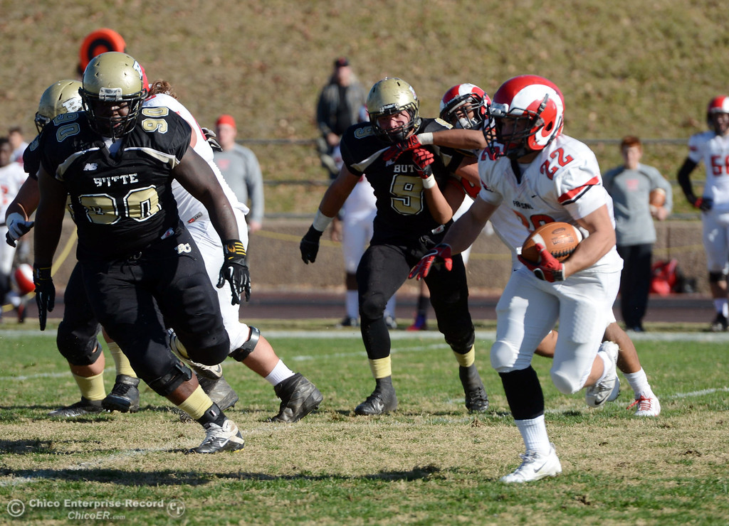 . Butte College\'s #90 Stephen Francois (left) and #9 Tyler Adair (center) defend against Fresno City College\'s #22 Alek Mechikoff (right) in the first quarter of their football game at Butte\'s Cowan Stadium Saturday, November 30, 2013 in Butte Valley, Calif.  (Jason Halley/Chico Enterprise-Record)