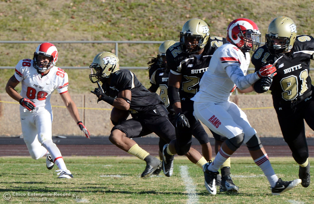 . Butte College\'s #1 Wes McCoy (center) returns a kickoff for a touchdown against Fresno City College in the third quarter of their football game at Butte\'s Cowan Stadium Saturday, November 30, 2013 in Butte Valley, Calif.  (Jason Halley/Chico Enterprise-Record)
