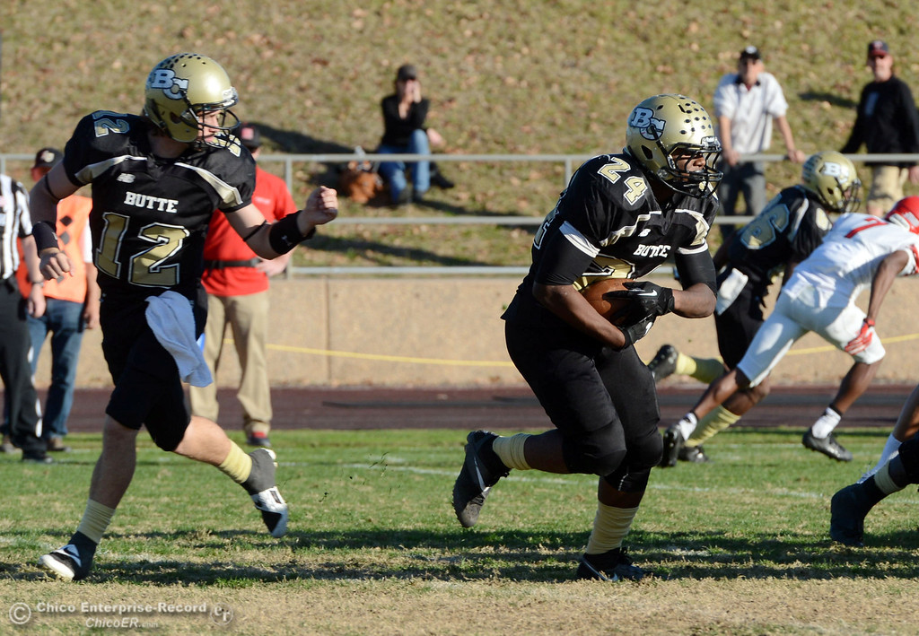 . Butte College\'s #12 Thomas Stuart (left) hands off to #24 Kendall Williams (right) against Fresno City College in the fourth quarter of their football game at Butte\'s Cowan Stadium Saturday, November 30, 2013 in Butte Valley, Calif.  (Jason Halley/Chico Enterprise-Record)