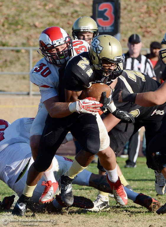 . Butte College\'s #21 Marvel Harris (right) is tackled against Fresno City College\'s #30 Tyler Bates (left) in the fourth quarter of their football game at Butte\'s Cowan Stadium Saturday, November 30, 2013 in Butte Valley, Calif.  (Jason Halley/Chico Enterprise-Record)