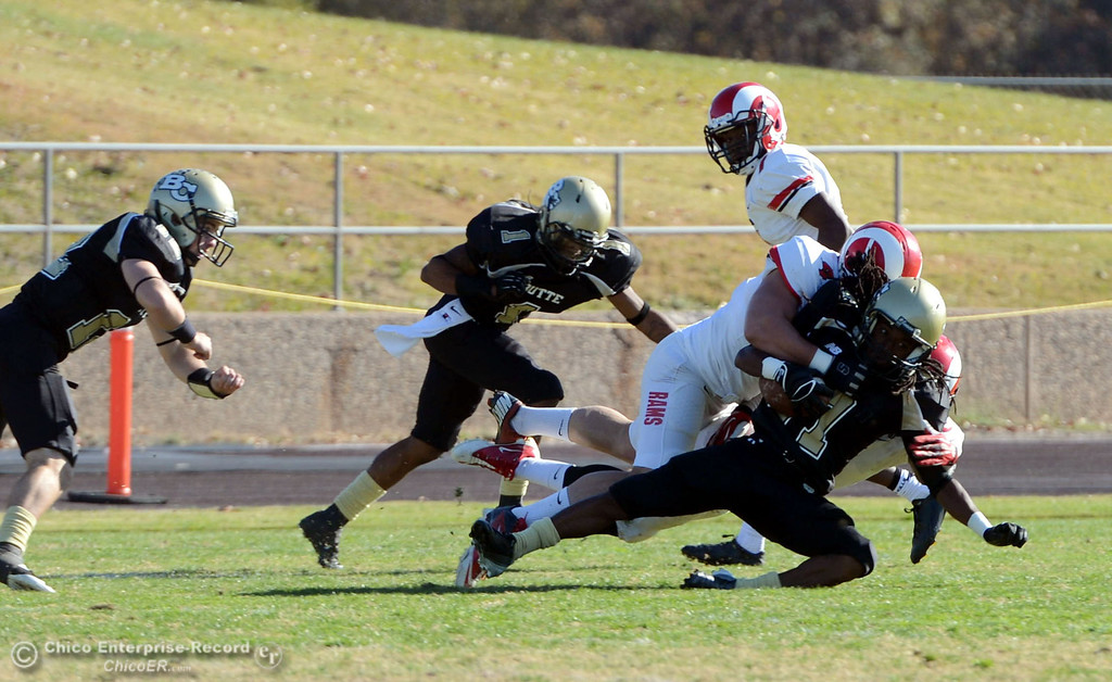 . Butte College\'s #87 Timazray Shepherd (center) is tackled against Fresno City College\'s #7 Vadal McDonald (back) in the second quarter of their football game at Butte\'s Cowan Stadium Saturday, November 30, 2013 in Butte Valley, Calif.  (Jason Halley/Chico Enterprise-Record)