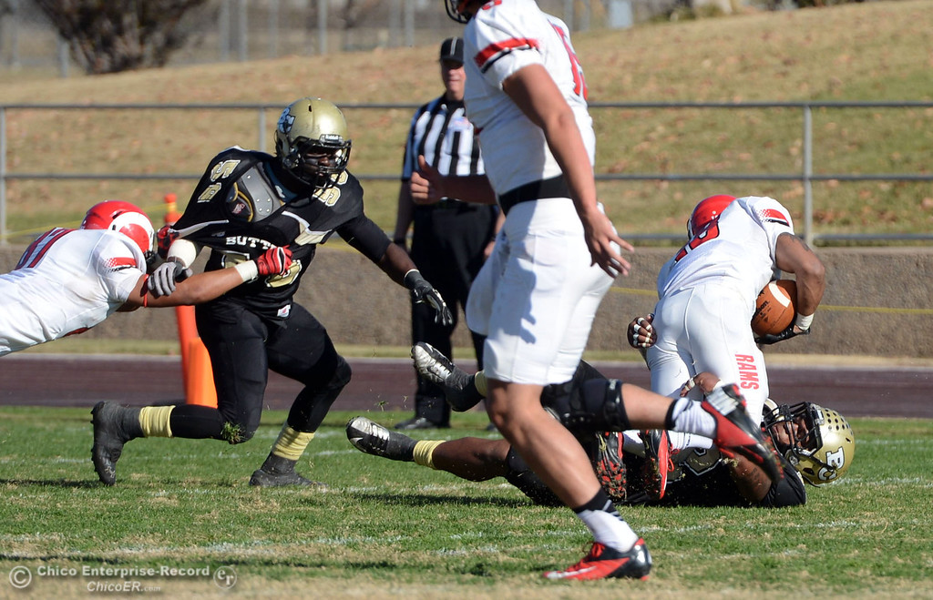 . Butte College\'s #32 Brian Anderson (bottom) tackles against Fresno City College\'s #18 Micah Ledezma (right) in the second quarter of their football game at Butte\'s Cowan Stadium Saturday, November 30, 2013 in Butte Valley, Calif.  (Jason Halley/Chico Enterprise-Record)