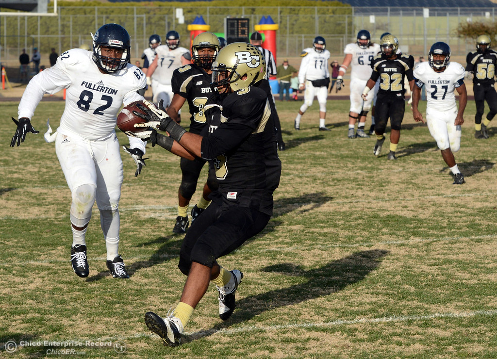 . Butte College\'s #3 London Muse intercepts a pass to return for a touchdown against Fullerton College in the fourth quarter of their CCCAA football state championship final at Butte\'s Cowan Stadium Saturday, December 14, 2013 in Butte Valley, Calif. (Jason Halley/Chico Enterprise-Record)