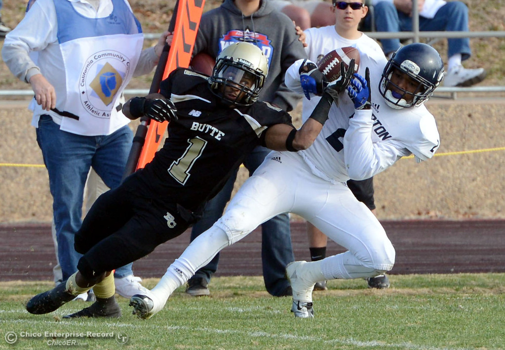 . Butte College\'s #1 Wes McCoy (left) attempts to break up a catch against Fullerton College\'s #2 Eli Pleasant (right) in the third quarter of their CCCAA football state championship final at Butte\'s Cowan Stadium Saturday, December 14, 2013 in Butte Valley, Calif. (Jason Halley/Chico Enterprise-Record)