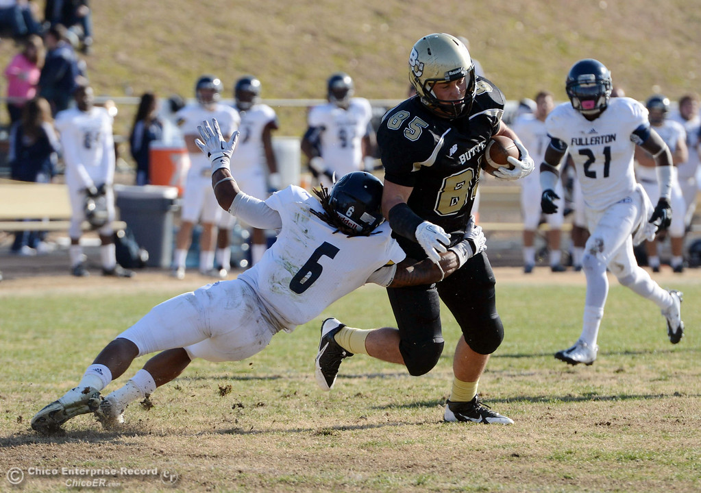 . Butte College\'s #85 Richard Murphy (right) breaks a tackle against Fullerton College\'s #6 Darius Lewis (left) in the first quarter of their CCCAA football state championship final at Butte\'s Cowan Stadium Saturday, December 14, 2013 in Butte Valley, Calif. (Jason Halley/Chico Enterprise-Record)